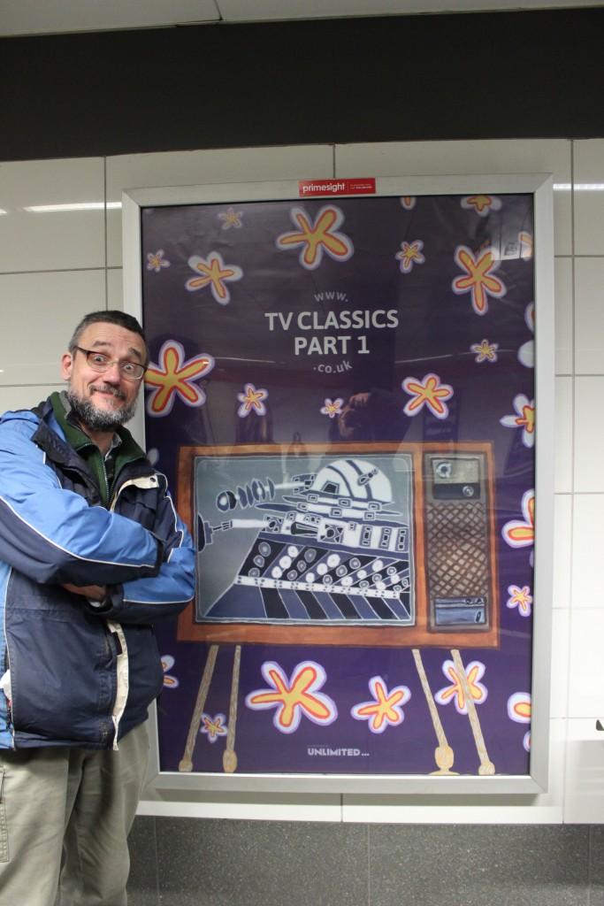 A photograph of artist Cameron Morgan stood next to a poster for his exhibition TV Classics Part 1, in a subway station. He is smiling
