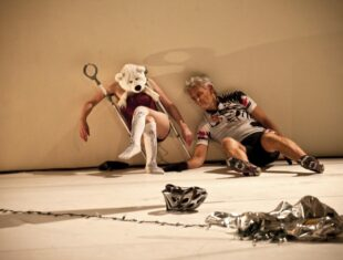 two dancers pose on the floor against the wall, one wears a teddy bear mask