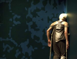 photo of bleach-haired performer Claire Cunningham in a darkened room, kneeling in a corner, with crutches