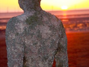 photograph taken at sunset of the back of Anthony Gormley's iron man from a sculptural placement at Crosby Beach in Merseyside. There are quite a few iron men placed at various intervals along the beach, meaning that the tide comes over them to varying extents. They are quite famous around Liverpool because people are always dressing the iron men up in all kinds of strange clobber. I like them so much because they are representative of stillness and movement, travelling and not, at the same time. It is a wonderful and inspiring place to visit.