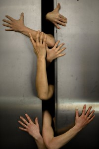 A series of arms come out of an open lift door grabbing out at it.