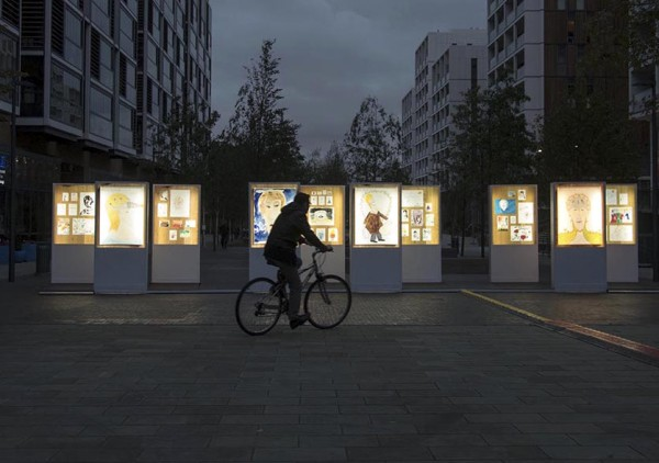 photo of a series of light boxes containing artwork are displayed outdoors at night-time