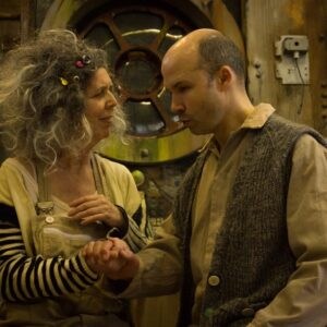 A photograph of actors Heather Gilmore as Old Woman (left) and Tim Gebbels as Old Man right in Extant's The Chairs. They are holding hands and seem deep in conversation. A dystopian set is behind them.