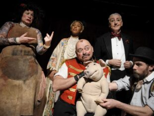 A production shot of Edmund the Learned Pig featuring the cast gathered around the pig puppet.