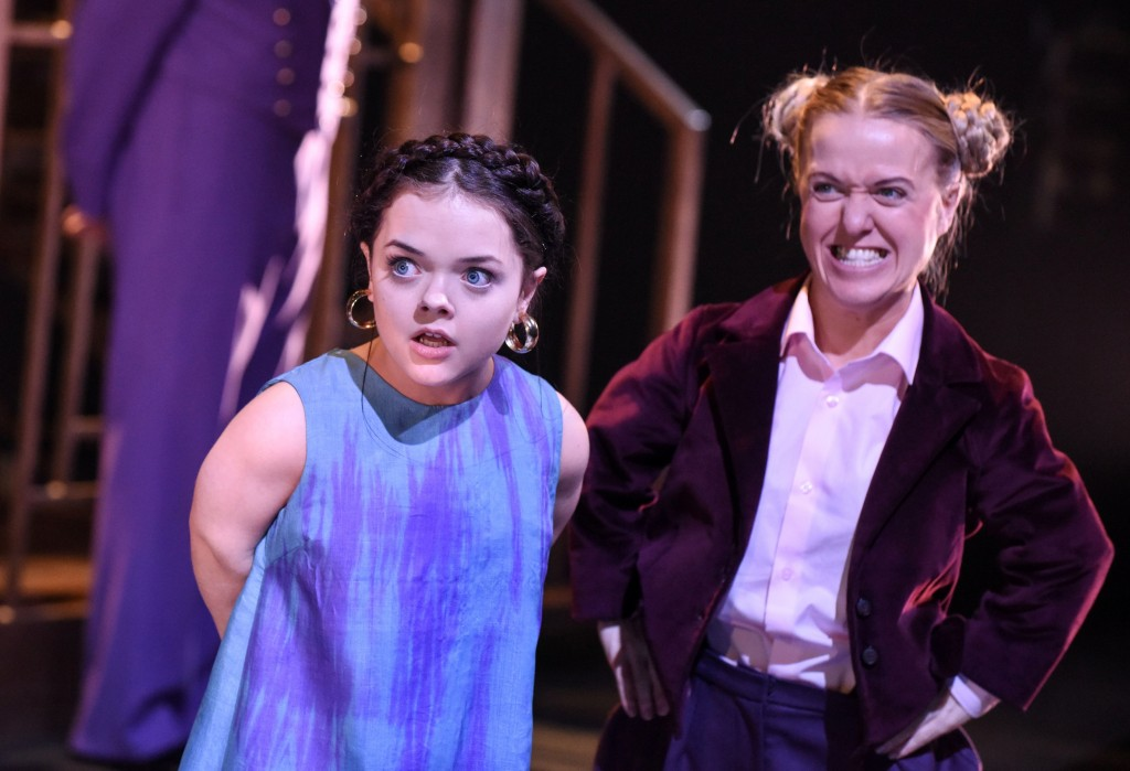 A photograph of Francesca Mills as Maria and Rachel Denning as Dobchinsky. The former is leaning in looking surprised while the latter has her hands on her hips and is laughing.
