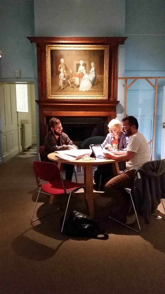photo of artist Juan delGado, film-maker Juan Soto and editor Manuel Angel Macia sat around a table within the confines of a gallery room in the Geffrye Museum. A framed Victorian painting hangs on a wall behind them.