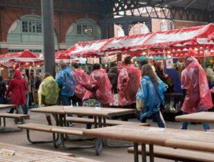 photo of a promenade performance under a red market tarpaulin