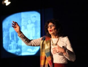 Photo of writer Lynne Blackwood performing against a black background, her hand raised forward in front of a blue projection of photographs.