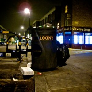 photo of a large black bin on a pavement in a busy London street at night - with the word 'LOONY' spelt across it in yellow