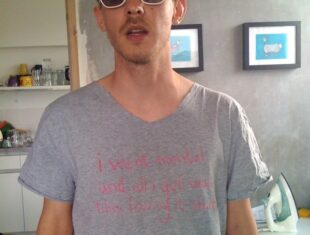 "portrait photo of James Leadbitter looking straight at the camera, wearing sunglasses and a grey t-shirt that says ""I went mental and all I got was this lousy t-shirt"""