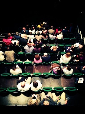 photo of a group of people sat in an auditorium as seen from above