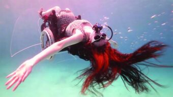 A photograph of Sue Austin in her underwater wheelchair, she is upside down with her arms out to the side.