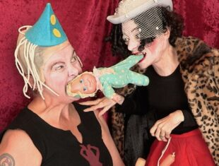 photo of performers Julie McNamara and Liz Carr in party dress, biting a dolly