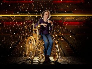 Liz Carr seated in a gold wheelchair on theatre stage
