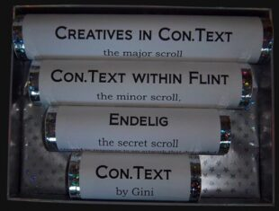 Four white tubes in decreasing lengths, displayed in a box lined with silver stars. Each tube has a title: 'Creatives in Con,Text, the major scroll; Con.Text within FLINT, the minor scroll; Endelig, the secret scroll and last but not least the shortest tube Con.Text by Gini. A simple solution, but what a dithering journey I took to get to this presentation.