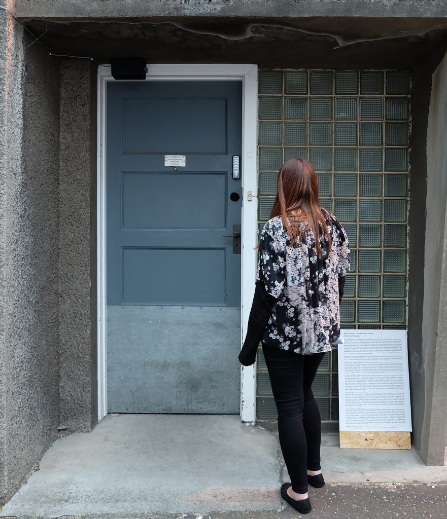 A photograph of a nondescript doorway, with a woman standing looking at it (her back to the camera), there is a speaker installed surreptitiously. This makes up Bekki Perriman's The Doorways Project, a sound installation.