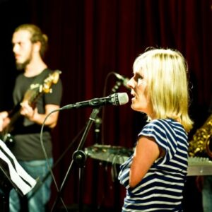 photo of female singer in front of a mike with musicians in an Un-Label workshop