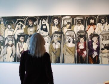 Image shows a woman in an art gallery looking with interest at a painting on the wall
