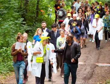 A photograph of a group of people involved in Daily Life Ltd's 'Roving Diagnostic Unit'. The group are walking through a wooded area, lead by artist Bobby Baker.