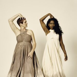 Sue MacLaine and Nadia Nadarajah stars of Can I Start Again Please? with very long dresses that sprawl out onto the floor. They both have their hands on their heads.