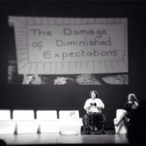 black and white photo of Jess Thom on stage with the slogan 'the damage of diminished expectations' behind her