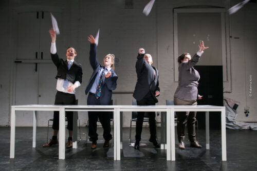 Promotional photograph for Silent Faces' show Follow Suit featuring the performers in oversized suits throwing paper aeroplanes.