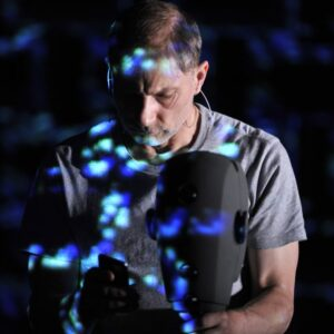 Photo of Simon McBurney lit in shadow and surrounded by blue lights