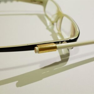 Photo outlining the attachment of the conductors baton to James Rose's glasses