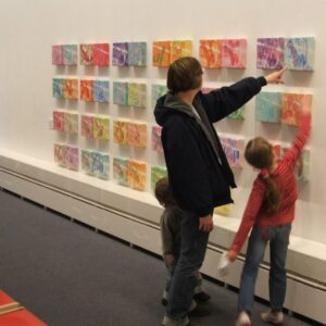 Exhibition shot of Esther Fox's painting installation a series of lines. An adult and two children are pointing at the work.