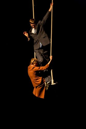 Photo of make and female performer together on a trapeze, dressed in suits