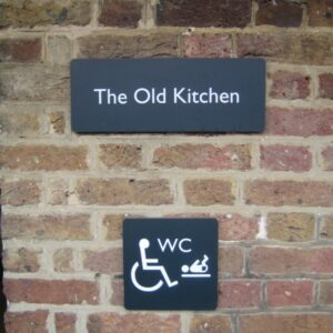 photo of a sign saying the old kitchen. Beneath is a disability sign for accessible toilet and changing room