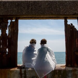 Two people partaking in the Last Resort sit in a dilapidated window frame overlooking the sea