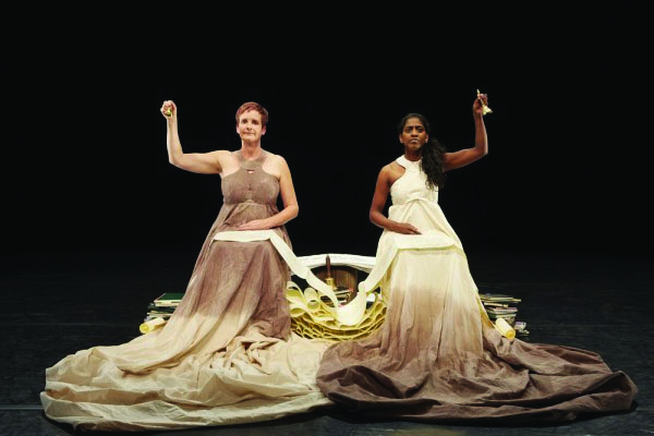 Sue MacLaine and Nadia Nadarajah sit side by side in contrasting Greco-Roman style dresses, each ringing a small bell and connected by a shared ream of paper.