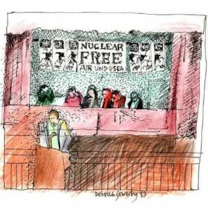 Drawn in black ink with muted colours - brown, red and green. Five seated figures on stage, behind a table. In front: someone makes a speech. Above: banners say 'Nuclear free air, land and sea.' Signed Deborah Sowerby, my other name