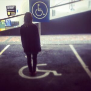 Image of artist standing in a disability parking space. Bewildered.