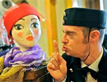 A photograph from Myth in Store. A lift attendant in a hat does a hush sign with his hand to a puppet, he is trying to keep a secret.