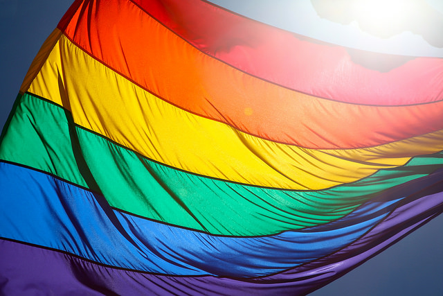 Photograph of a rainbow flag, the sun shining behind it.