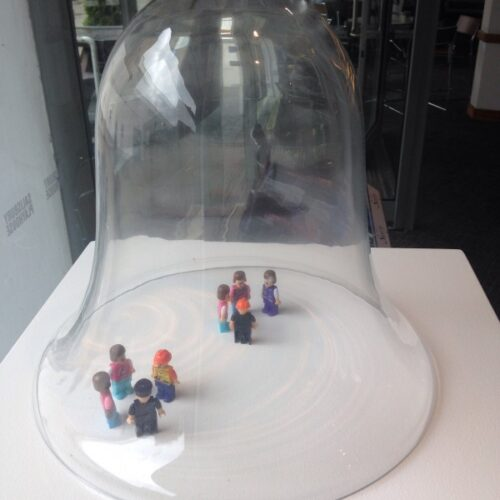 A photograph of two sets of lego minifigures under a bell jar