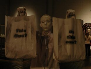 """A photo of Tim Jeeves facing the camera. He is dressed in a white shirt, wearing white make-up on his face and hands, and his hair is dyed white and slicked back. He is holding up two white paper bags; the bag in his right hand (on the left of the photo) has 'This one?' written on it, whilst the other is labelled 'Or this one?"""""""