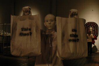 A photo of Tim Jeeves facing the camera. He is dressed in a white shirt, wearing white make-up on his face and hands, and his hair is dyed white and slicked back. He is holding up two white paper bags; the bag in his right hand (on the left of the photo) has 'This one?' written on it, whilst the other is labelled 'Or this one?""