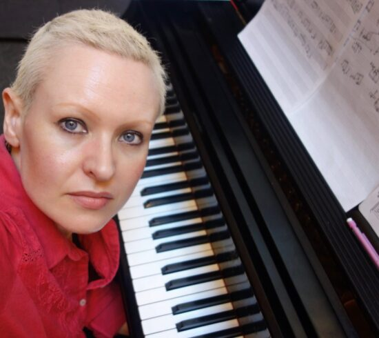 Female with short blonde hair in red top sitting at piano keyboard