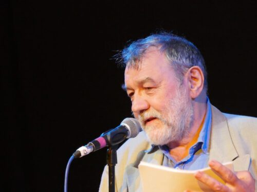 photo of disabled performer Allan Sutherland reading from his poetry collection