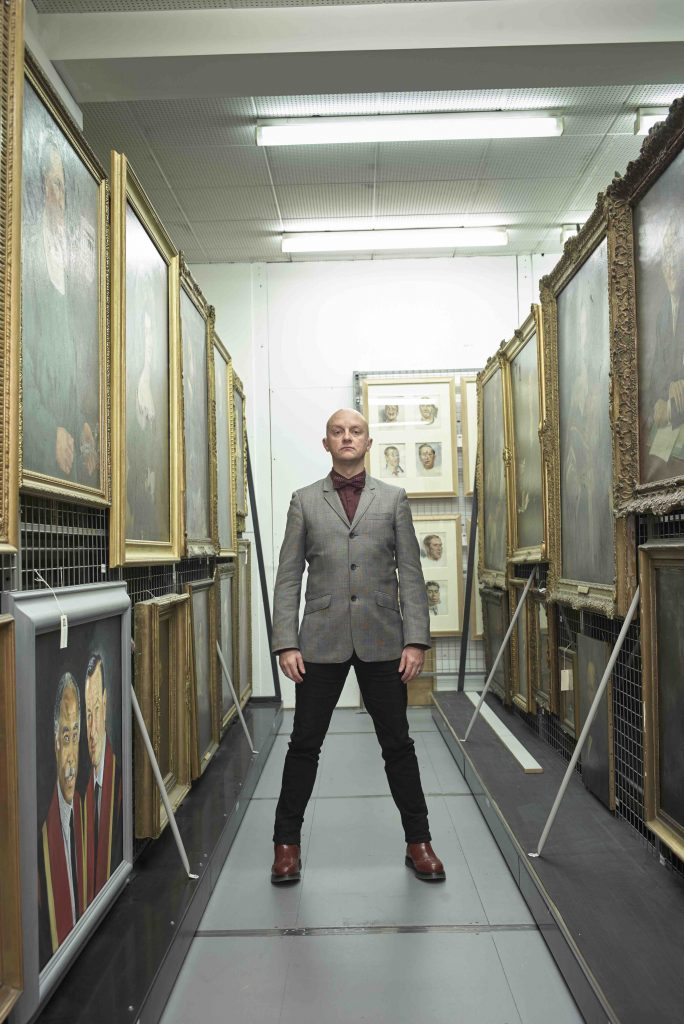 Photo of dancer Mark Smith dressed in a suit, posing in an museum archive