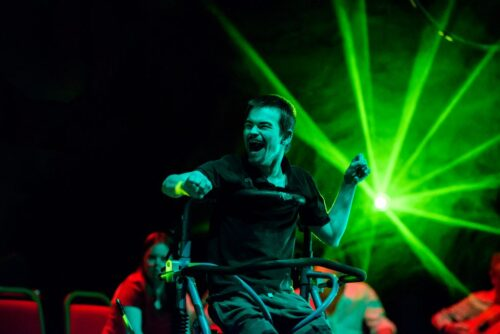 Photograph of a performer from Extraordinary Bodies, he is dancing with a pleased expression on his face, a green light dissipates in the background.