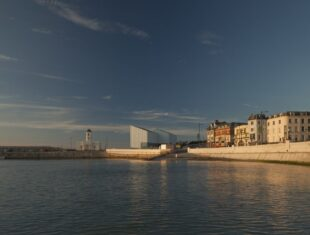 A photograph of Turner Contemporary gallery, overlooking the seaside with water in front and clear blue skies above.