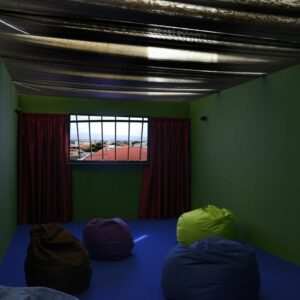 Gillian Wearing's installation A Room with Your Views, a green room with beanbags and a screen showing the video work with curtains either side.
