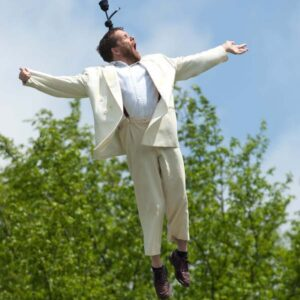 photo of disabled performer Jamie Bedard flying through the air on a wire, dressed in a white suit