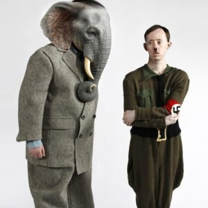 photo of an actor dressed as an elephant standing next to an actor dressed as Hitler