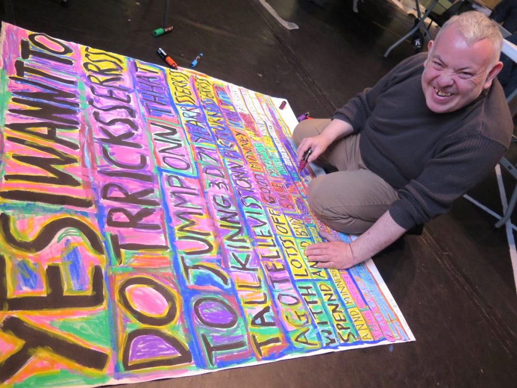 photo of an artist kneeling on the floor with a large multicoloured poster, smiling at the camera