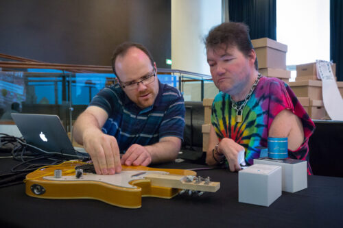 A photograph of musician John Kelly and coder Charles Matthews working on an adapted guitar, Cahrles is tweeking something on the body of the guitar, which has a reduced size neck.